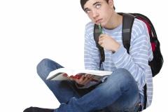 Junger männlicher Student mit Buch lernt und denkt nach